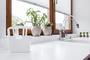 Blaty w kuchni zostały wykonane z białego Corianu, do tego zlewozmywak wpuszczany w blat od Duravit i bateria Esprit od Kludi – tworzą spójną, jednolitą kompozycję.