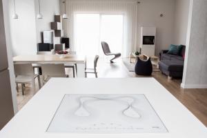 Z perspektywy wyspy pięknie widać całą strefę dzienną. Biała płyta indukcyjna od Gorenje została zaprojektowana przez Karima Rashida i jest designerskim dziełem sztuki.
