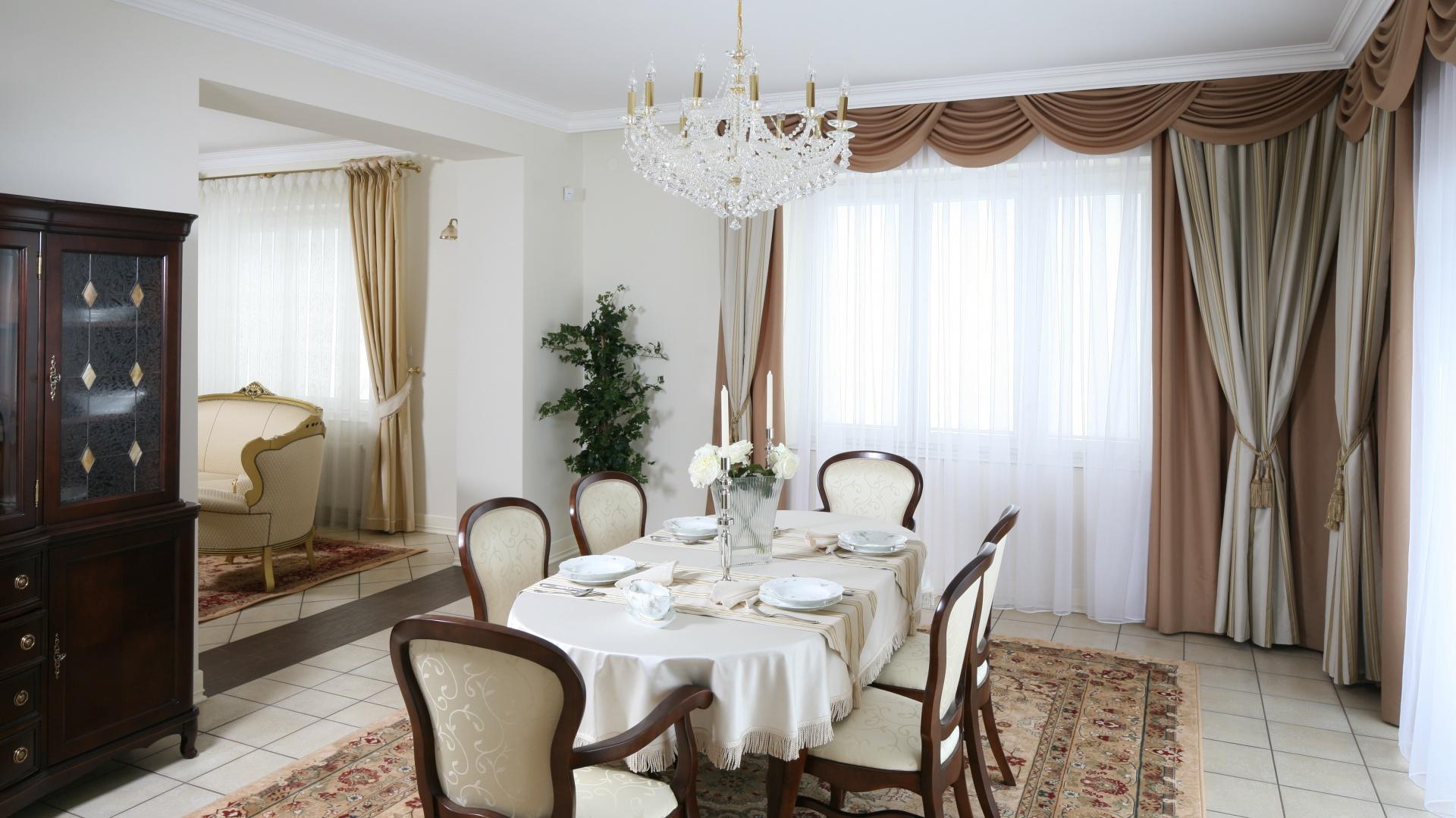 """Na dużym, drewnianym stole dumnie prezentuje się efektowny serwis obiadowy """"Louis"""" z XIX wieku – jeden z najstarszych modeli firmy Rosenthal. Cienkościenną porcelanę zdobi delikatny relief – neorokokowy wzór, uzupełniony eleganckimi kwiatowymi gałązkami i złoceniami. Projekt wnętrza: Małgorzata Goś. Fot. Bartosz Jarosz."""