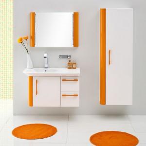 Nowoczesna kolekcja mebli łazienkowych Pantone marki Antado z pojemnym regałem, których białe fronty zdobią intensywne pomarańczowe dekory. Fot. Antado.