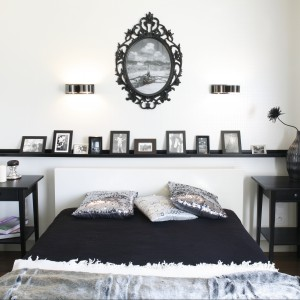 Nad łóżkiem znajduje się galeria fotografii umieszczona na czarnej półce oraz główne zdjęcie oprawione w ozdobną ramę. Proj. Małgorzata Mazur. Fot. Bartosz Jarosz.