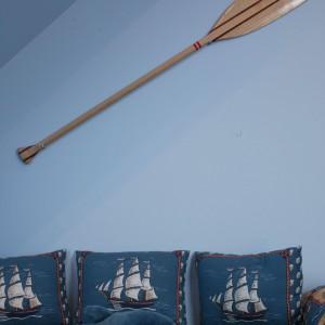 Wiosło zawieszone na ścianie przy łóżku to oryginalny pomysł na dekorację ściany.