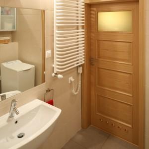 Prosta forma grzejnika doskonale wpisuje się w ciepła aranżację przestrzeni łazienki. Projekt Iza Szewc. Fot. Bartosz Jarosz.