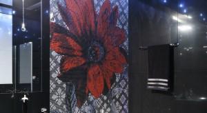 """Łazienka skąpana jest w czerni, z wyjątkiem ściany, na której """"wyrósł"""" ogromny, czerwony kwiat."""