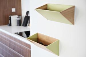 Kuchnia z wyspą. Urządzona minimalistycznie, bez zbędnych elementów, nie traci ciepła dzięki zabudowie w jasnobrązowym kolorze. Jej układ z pewnością usprawni pracę - do dyspozycji jest wyspa kuchenna, a każdy sprzęt znajdzie swoje miejsce w jednej z wielu szafek. W razie potrzeby również kuchnia może stać się jadalnią - stół z kilkoma krzesłami jest bowiem jej integralną częścią.  Nie brakuje tutaj też intrygujących dodatków i detali, czyniących ją bardziej funkcjonalną - wiszące półki na wyspą czy schowki na drobiazgi przypominają, że diabeł tkwi w szczegółach.
