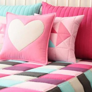 Narzuta na łóżko w kolorowe kwadraty. Pastelowe odcienie skontrastowano z ciemnymi elementami. Fot. Patchwork House / Pakamera.