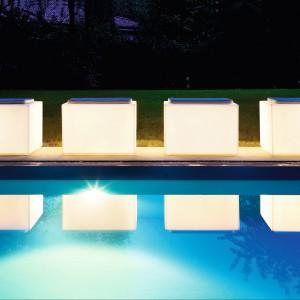 Duże, białe siedziska o zgeometryzowanej bryle z oferty firmy Varaschin nocą pełnią funkcje lamp. Fot. Varaschin.