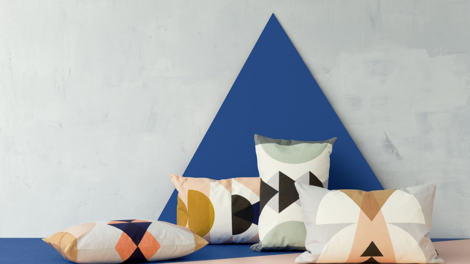 Dekoracyjne poduszki z geometrycznymi nadrukami wykonane z bawełnianego płótna. Fot. Ferm Living.