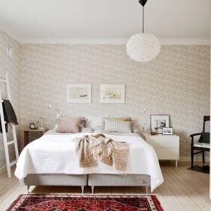 Jasną sypialnię możemy ożywić za pomocą tkanin, np. kolorowego dywanu. Fot. Stadshem.