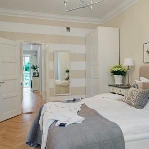 Ściana w sypialni ozdobiona dekoracyjnymi białymi i beżowymi pasami. Fot. Alvhem Makleri.