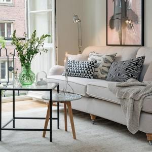 Jasna kanapa na nóżkach w duecie z prostymi skandynawskimi stolikami. Fot. Alvhem Makleri.