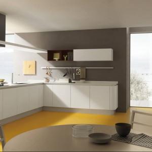 Meble z kolekcji Primavera firmy Febal Casa. Białe, gładki fronty otwierane bezuchwytowo. Na szarej ścianie fajnie prezentuje się reling wiszący nad blatem. Nietypowa podłoga w żółtym kolorze ożywia spokojne, stonowane wnętrze. Stanowi jednak harmonijną i bardzo spójną całość. Projekt: Matteo Thun i Antonio Rodriguez.