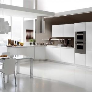 Meble z kolekcji Life firmy Stosa. O prostej, nowoczesnej formie. Gładkie, białe fronty otwierane są przez lekkie naciśniecie. Fajnie prezentuje się reling wiszący na ścianie nad blatem.