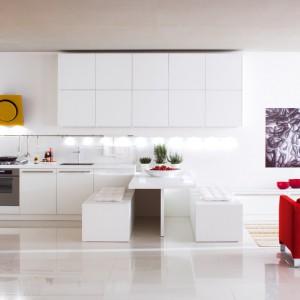 Meble z kolekcji Ethica firmy Veneta Cucine. Idealnie sprawdzą się w kuchni otwartej na salon. Zapewniają ogromną powierzchnię przechowywania – szafki wiszące, zabudowa dolna i wysoka. Żółty okap tworzy ciekawy kontrast zarówno z białymi frontami, jak i z czerwoną kanapą w salonie. Warto zwrócić uwagę również na półwysep pełniący rolę stołu oraz dość nietypowe siedziska.