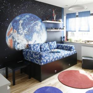 Z kolorystyką dekoracji ściennej harmonizuje czarno-niebieska sofa pełniąca funkcję łóżka. Fot. Archiwum Dobrze Mieszkaj.