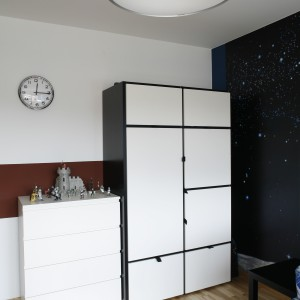 Szafa z czarno-białymi frontami oraz nowoczesna komoda tworzą strefę przeznaczoną do przechowywania garderoby. Fot. Archiwum Dobrze Mieszkaj.