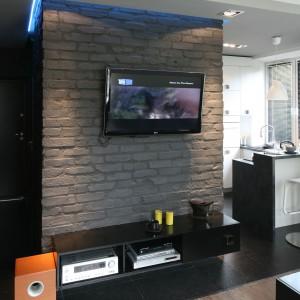 W małym mieszkaniu urządzonym w czarno-białej minimalistycznej stylistyce motyw cegły przewija się we wszystkich jego pomieszczeniach. Pomalowana na szaro cegła stała się też oryginalnym panelem po telewizor. Projekt Dominik Respondek. Fot. Bartosz Jarosz.