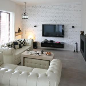 Chłodny klimat salonu ocieplają miękkie, pikowane kanapy w stylu chesterfield, drewniana podłoga i stylowe oświetlenie. W takim otoczeniu nawet surowa, wyłożona białą cegła ściana ściana wydaje się nieco bardziej przytulna. Projekt Monika Włodarczyk, Jarosław Włodarczyk. Fot. Bartosz Jarosz.