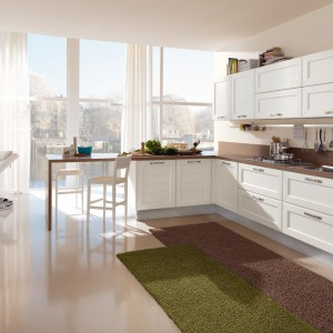 Meble z kolekcji Claudia firmy Lube Cucine. Białe fronty szafek z wyraźnie zaznaczonymi, poziomymi dekorami imitującymi deski doskonale współgrają z chromowanymi uchwytami. Drewniany blat nie tylko ociepla kuchnię, ale z jednej strony przechodzi w praktyczny stolik.