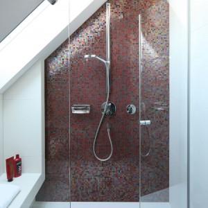 Szklana mozaika, mieniąca się różnorodnymi odcieniami czerwieni i fioletów, dekoruje ścianę za prysznicem. Niczym kobieca biżuteria stanowi ona niezwykle elegancką ozdobę utrzymanej w bieli i drewnie łazienki. Projekt Magdalena Konopka, Marcin Konopka. Fot. Bartosz Jarosz.