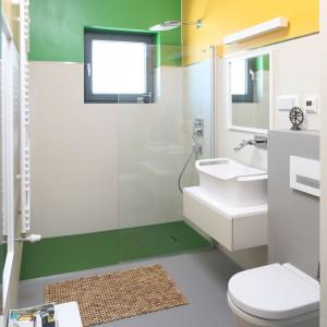 Biel i szarość przeważają w tej łazience, podkreślając jej nowoczesny charakter. Jednak barwne akcenty wymalowań ścian zdają się dominować nad wnętrzem, tworząc je ciepłym i radosnym. Gdy się już opatrzą, w prosty sposób można je zamienić na bardziej stonowane. Projekt Konrad Godziński. Fot. Bartosz Jarosz.