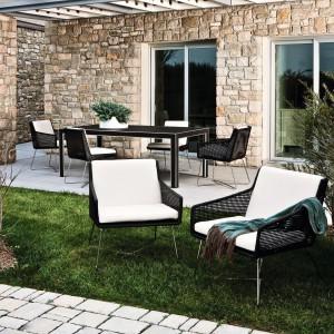 Przestronne, wygodne fotele z kolekcji Avalone marki Varaschin wykonane z ekorattanu osadzone zostały na krzyżakowej podstawie z aluminium. Czarny kolor podstawy siedziska doskonale kontrastuje z dużymi, białymi poduchami. Fot. Varaschin.