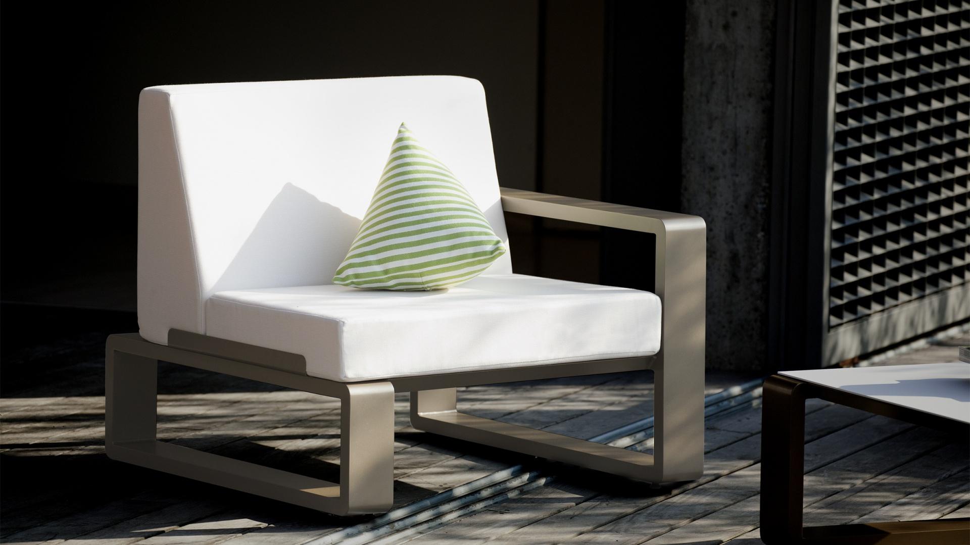 Fotel z kolekcji mebli modułowych Kama marki Ego Paris. Białe, tapicerowane siedzisko zostało osadzone w jasnobrązowej ramie o ciekawym kształcie. Fot. Ego Paris.