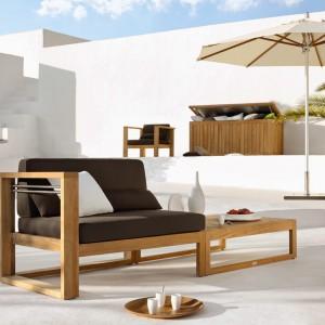 Duży, wygodny fotel z kolekcji mebli modułowych marki Manutti zintegrowany ze stolikiem. Całość wykonana została z drewna teakowego. Fot. Manutti.