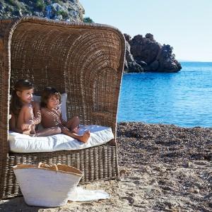 Dwuosobowa sofka z ciekawym zadaszeniem marki Riviera Maison. Ciepły, miodowy kolor rattanu podkreśla jej wakacyjny urok. Fot. Riviera Maison.