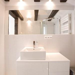 Ciemne drewno belek stropowych w parze z bielą wspaniale się prezentuje. To ciepły i naturalny materiał, który wprowadził do wnętrza nieco dynamiki.