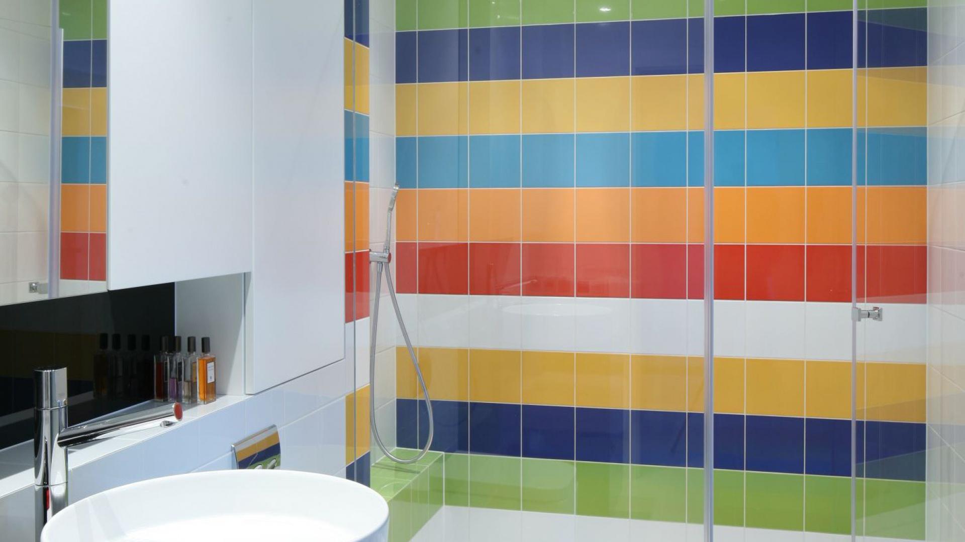 Łazienka jest bardzo odważną kompozycją barwnych zestawień. Mnogość kolorów płytek ceramicznych wraz  z białymi ścianami i czarną szafką podumywalkową tworzą spójną stylistycznie całość. Projekt Katarzyna Kiełek, Agnieszka Komorowska-Różycka. Fot. Bartosz Jarosz.