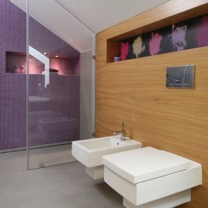 Łazienka jest na tyle duża, że bez problemu wygospodarowano miejsce na wannę, prysznic oraz dwie umywalki. Dwie przeciwległe ściany zdobi piękna, fioletowa mozaika. To jedyny tak mocny kolorystycznie akcent w tym wnętrzu. Projekt Małgorzata Galewska. Fot. Bartosz Jarosz.