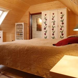 W sypialni dominuje drewno, które znajdziemy na podłodze, ścianach i suficie, dzięki czemu jednakowa, ciepła kolorystyka płynnie otacza całą sypialnię. Proj. Kubasik Agnieszka. Fot. Bartosz Jarosz.