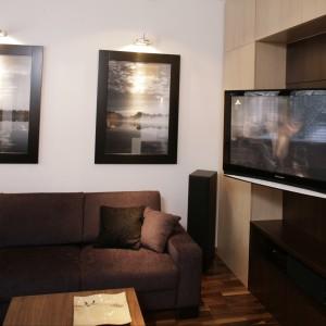 Zdjęcia oprawione w czarne ramy przypominają ekrany telewizorów. Projekt: Hola Design. Fot. Archiwum Dobrze Mieszkaj.