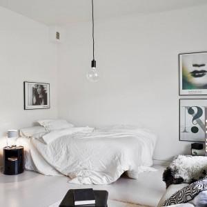 Jasną sypialnię wzbogacono ciemnymi dodatkami - stolik nocny, ramki na obrazy. Fot. Stadshem.
