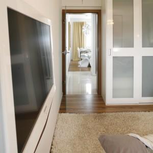 Na przeciwko łóżka, na ścianie znajduje się telewizor w białej obudowie. Proj. Małgorzata Mazur. Fot. Bartosz Jarosz.