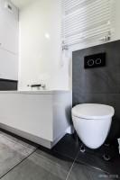 Biała łazienka z szarymi akcentami.