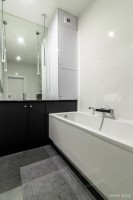 Okrągłe uchwyty i oryginalna mozaika dodają klasycznej elegancji tej niewielkiej łazience.