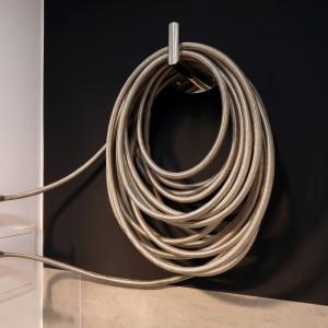 Najciekawszym elementem wystroju tej łazienki wydaje się być dekoracyjny grzejnik. Jego oryginalna forma, przypominająca zwinięty wąż ogrodowy idealnie podkreśla loftową stylistykę wnętrza. Projekt Justyna Smolec. Fot. Bartosz Jarosz.