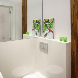Kompozycję okładzin ściennych uzupełniają białe płytki ceramiczne, których duży format dodatkowo powiększa łazienkę.  Narożny sedes o ciekawej stylistyce i oryginalnej formie doskonale sprawdził się w tym niewielkim pomieszczeniu. Projekt Katarzyna Merta-Korzniakow. Fot. Bartosz Jarosz.