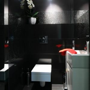 Czarną przestrzeń łazienki rozświetla punktowa biel obecna na ceramice oraz szafce pod umywalkę. Tę ostatnią wyposażono w biżuteryjny uchwyt. Projekt Łukasz Sałek. Fot. Bartosz Jarosz.