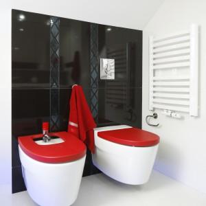 W strefie toalety białe płytki ceramiczne zestawione zostały z czarnymi. Na tym tle wyróżniają się czerwone deski – sedesowa i bidetowa. Projekt Marta Kilan. Fot. Bartosz Jarosz.
