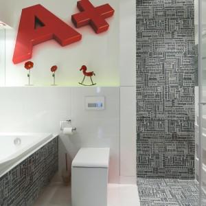Poza czerwonymi akcentami w łazience, uwagę przyciągają czarno-białe płytki z przypominającymi prasowe nagłówki nadrukami. Projekt Katarzyna Mikulska-Sękalska. Fot. Bartosz Jarosz.