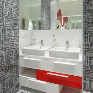 Intensywna czerwień to dominanta stylistyczna tej łazienki. Króluje nie tylko na dodatkach, ale też frontach wykonanej na zamówienie szafki pod umywalkę.Projekt Katarzyna Mikulska-Sękalska. Fot. Bartosz Jarosz.