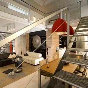 W urządzone w nowoczesnym, nieco industrialnym stylu wnętrzu panuje niezwykły ład kompozycyjny. Wszystko ma tu swoje starannie zaplanowane i wytyczone miejsce. Przestrzeń salonu organizuje drewniana okładzina na ścianie i podłodze. Projekt Lilianna Masewicz-Kowalska. Fot. Marcin Onufryjuk.