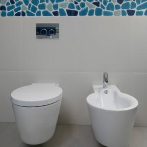 Ściana z podwieszaną ceramiką sanitarną została wyłożona białymi płytkami. Dodatkowo zdobi ją pas mozaiki. Projekt Małgorzata Galewska. Fot. Bartosz Jarosz.