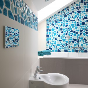 Wszechobecne w całym projekcie biele i szarości w łaziance zeszły na plan drugi, tworząc eleganckie tło dla morskiej mozaiki. Projekt Małgorzata Galewska. Fot. Bartosz Jarosz.