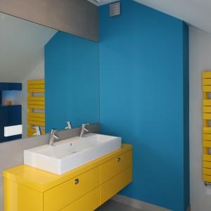 Duża żółta szafka zaprojektowana została aż pod dwie umywalki. Jej słoneczna barwa doskonale koresponduje z kolorem dekoracyjnego grzejnika umieszczone na przyległej ścianie. Projekt Małgorzata Galewska. Fot. Bartosz Jarosz.