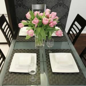 Sześcioosobowy stół ze szklanym blatem dumnie zdobią wiosenne tulipany. Projekt Magdalena Wielgus-Biały. Fot. Bartosz Jarosz.