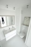 Łazienka utrzymana w bieli. Subtelnej ozdobności nadają jej kafelki z delikatnym wzorem oraz lustro w srebrnej ramie. Jest przy tym również funkcjonalna – dzięki półkom i szafkom nie zabraknie w niej miejsca na potrzebne drobiazgi.